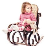 Mädchen schaukelt mit Stofftier im Kinder-Schaukelstuhl