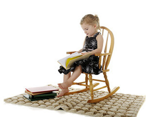 Kleines Mädchen sitzt im Kinder-Schaukelstuhl und erfreut sich an Büchern